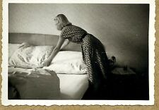 Young woman making bed faceless graceful motion unusual snapshot vintage