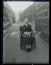 Glass negative - Elderly Lady relaxing in easy chair at the end of the street.