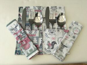 A pair of christmas cutlery and napkin table settings festive design cotton