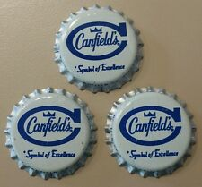 Three CANFIELD'S unused bottle caps.