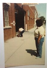 Vintage 70s Found PHOTO Young Lady Watches Friend Carrying Way Too Much Luggage