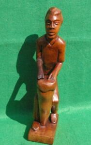 CARVING OF A STANDING AFRICAN MALE DRUMMER IN MID BROWN HARDWOOD