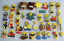 A collection of different Marie Curie pin badges and key rings charity