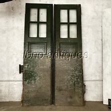 PAIR OF 1940s VINTAGE INDUSTRIAL WOODEN DOORS W/ GLASS PANES AND STEEL PLATES.