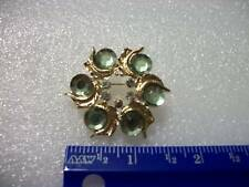 Gold plated pin with round green stones