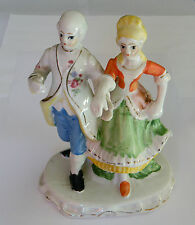 UNMARKED POTTERY FIGURINE OF A REGENCY COUPLE OUT FOR A STROLL