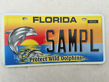 """FLORIDA MINT SAMPLE LICENSE PLATE """" SAMPL """"  FL  PROTECT WILD DOLPHINS GRAPHIC"""