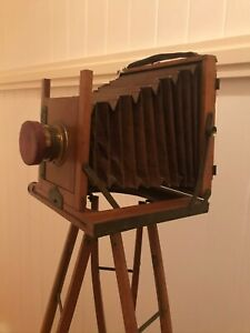 Antique wooden and brass folding camera with bellows and tripod