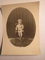 Auf einem Stuhl sitzendes kleines Kind mit Spielzeug Bär Teddybär / Foto