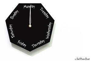 DayClocks - Heptagon Black Wall Clock - Day of The Week Clock - Fun Clock Gift