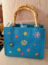 Purse with flowers and bamboo handles with a magnetic closure.