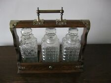 An antique Victorian oak three cut glass decanters tantalus with s/p mounts.