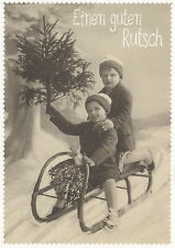 Neujahrskarte: Zwei Kinder auf dem Schlitten mit Weihnachtsbaum: Guten Rutsch