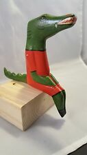 handcrafted wooden Alligator sits on edge of shelf