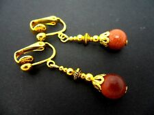 A PAIR OF BROWN GOLDSTONE  GOLD PLATED DANGLY CLIP ON  EARRINGS. NEW.