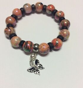 Stretch beaded bracelet orange black patterned beads butterfly clip on charm