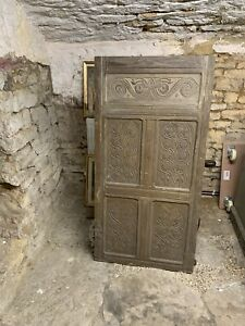17th CENTURY CARVED OAK CUPBOARD DOOR WITH CARVED PANELS AND TWO IRON HINGES