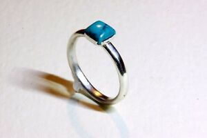 A pretty hand made solid sterling silver ring with turquoise stone size M