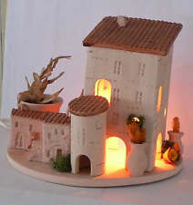 Une petite maison provençale en poterie avec un éclairage intérieur