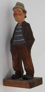 Man with sly grin carved wood figure by