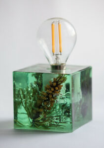 Green epoxy resin lamp with young shoots of mountain Italian pine