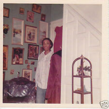 Black lady shows collection of pictures on wall 90802