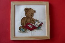 Completed cross stitch teddy bear reading a book in frame