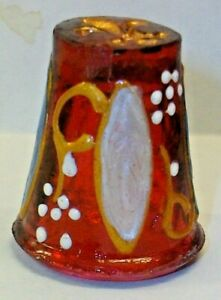 """AN UNUSUAL RED GLASS THIMBLE WITH AN ABSTRACT ENAMELED PATTERN """"CREST ON TOP"""""""