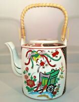 Oriental style teapot featuring blossoms, wagon & bird with a wicker handle