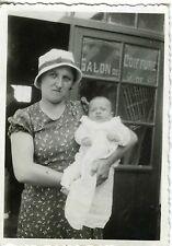 PHOTO / Snapshot / une femme pose avec son bébé devant un salon de coiffure 1930