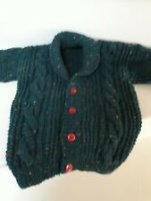 Infants hand crafted emerald green flecked cable knit cardigan with red buttons.
