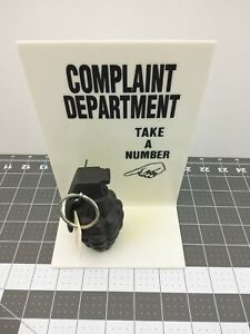 Complaint Department Sign Take Number Attached to a Replica Hand Grenade