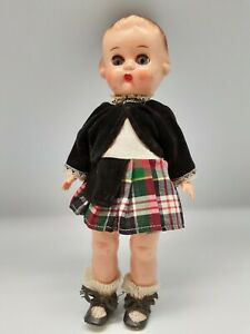Vintage moveable limbs doll in plaid dress with black velvet coat