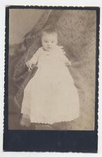 CABINET CARD OF BABY BEING HELD BY HIDDEN PERSON.