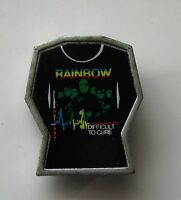 RAINBOW DIFFICULT TO CURE T-SHIRT SHAPED METAL PIN BADGE FROM THE 1980's ROCK