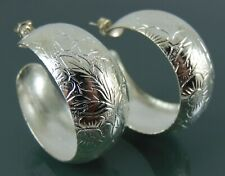 Thick hoop silver earrings embossed with a flower design