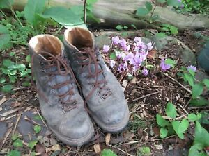 Old well used grubby mens gardening boots for display prop quirky garden planter
