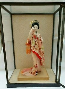 Vintage Japanese Geisha Doll on wooden base in glass display case.