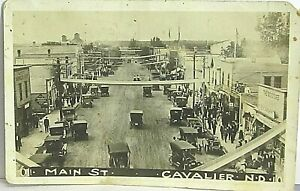 Vintage 1913 RPPC MAIN ST., CAVALIER, ND postcard w early autos, signs, people