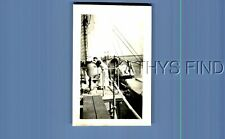 FOUND B&W PHOTO G+7467 VIEW OF MAN LEANED OVER ON SHIP,LIFEBOATS ON SIDE