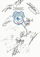 An A4 white card with the Cardiff City Badge. Signed by 13 players on 21.11.15.