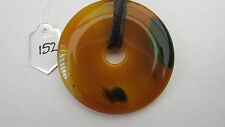 A YELLOW & GREEN DOUGHNUT AGATE PENDANT ON A WAXED CORD NECKLACE. (152)