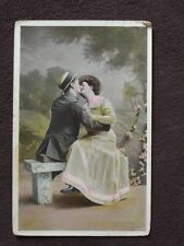 COUPLE SITTING ON PARK BENCH KISSING, COLOR TINTED POSTCARD