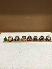 Group Of Seven Buddha Type Mini Figurines On Wood Board