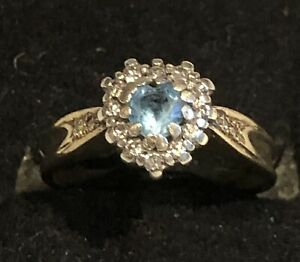 Rare 9ct gold ring set with central heart cut aquamarine bordered by diamonds.