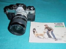 CANON AE-1 PROGRAM SLR CAMERA WITH 28-70 MM LENS AND INSTRUCTION BOOKLET
