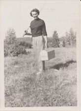 PORTRAIT OF SMILING YOUNG WOMAN W/ FISHING GEAR
