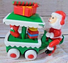 Vintage Santa Claus pedals vendor cart with gifts red green white plastic moves