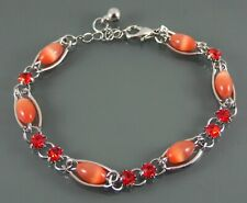 SILVER BANGLE BRACELET WITH PINK GLASS AND FACETED RED CUBIC ZIRCONIA BEADS.