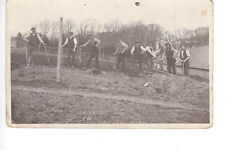 Line up of agricultural workers with spades. Fencing?